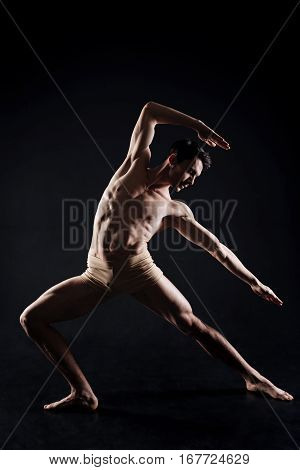 The art of yoga. Muscular confident skilled man stretching in the black studio and showing his skills while practicing yoga