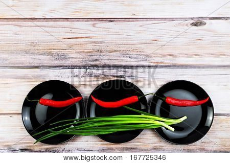 Red peppers on black dish. Green onions on black shiny plates. Vegetables in plates over wooden background. Colorful food background. Free space for text on wood backdrop.