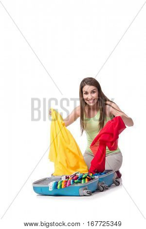 Young woman packing for summer vacation isolated on white