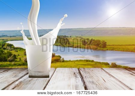 Milk pouring in glass. Close up of milk splash. Milk in glass on wood table. Glass with white milk on sunrise background. Colorful beverage background.