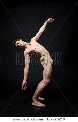 Involved in my performance. Involved flexible charismatic gymnast demonstrating his flexibility and expressing grace while dancing in the black colored room