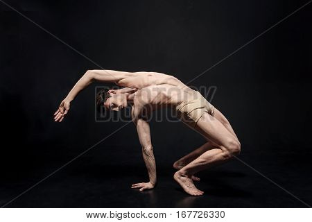 Facing another flatness. Concentrated flexible charming gymnast demonstrating his flexibility and expressing grace while performing in the black colored studio