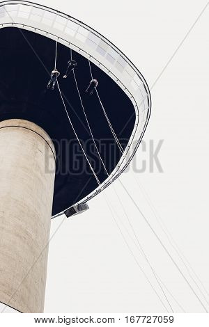 ROTTERDAM THE NETHERLANDS - AUGUST 23 2014: Three people abseiling from the Euromast tower Rotterdam the Netherlands