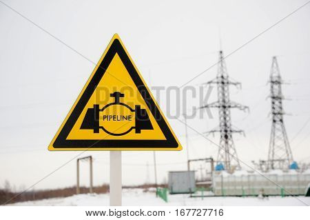 Pipeline sign with hight voltage power transmission tower. Power supply, oil and energetics concept.