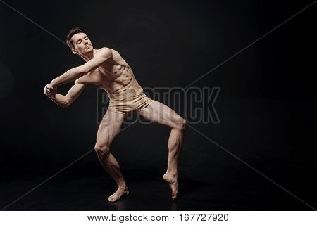 My vision of futuristic art . Athletic ingenious young athlete dancing against black background and showing his skills while expressing his vision of the futuristic art