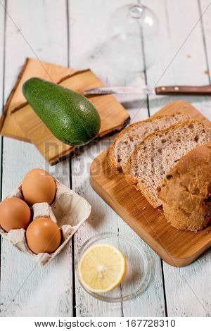 preparing a toast with eggs and avocado in the kitchen