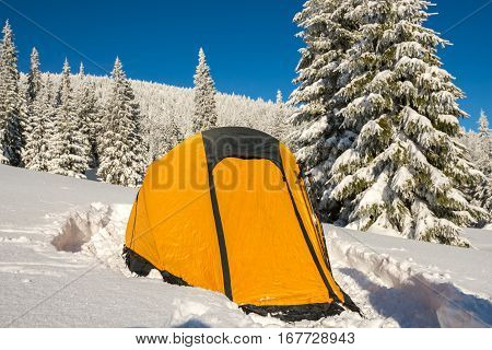 Yellow tent - close up at alpine meadow among the snow-covered firs on background panorama of mountains and colorful sky - magic winter adventure.