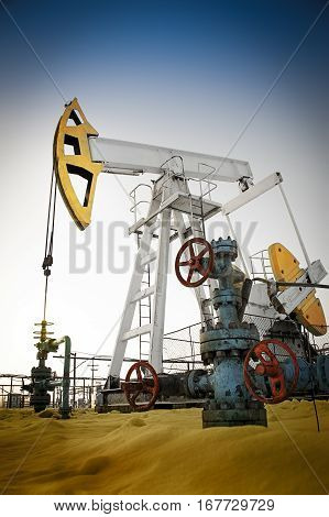 Oil pump jack and wellhead in the oilfield. Oil and gas concept.