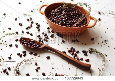 handcarved wooden spoon with kidney beans on white background
