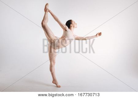Graceful like a swan. Elegant graceful young ballet dancer demonstrating her abilities and expressing tenderness while dancing in the white studio and standing on the tiptoe