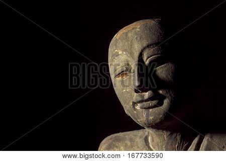 Buddhist monk carving in the form of an aged relic Face showing serene contentment.