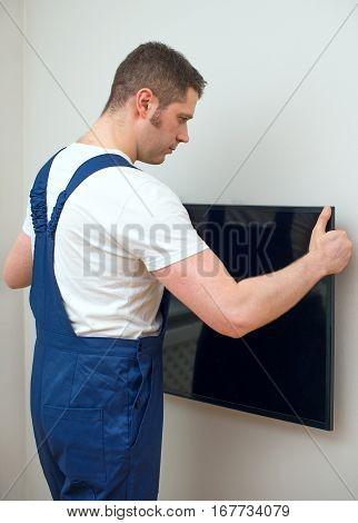 Young man mounting TV on the wall.