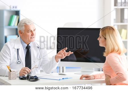 Young woman consulting with doctor at clinic