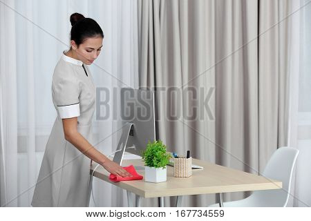 Female chambermaid cleaning in hotel room