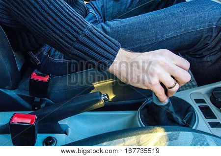 Man's hand on a mechanical gearbox in the car