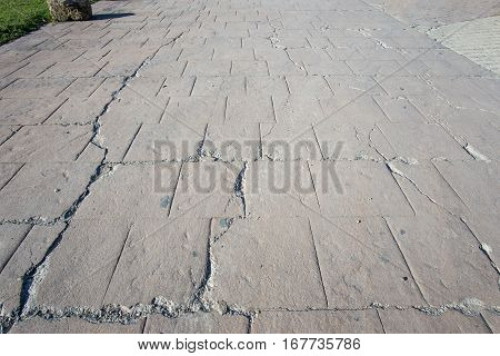 big break on damaged stamped fissure concrete cracked pavement, timeworn appearance colors textures of paving slate stone tile on cement, broken flooring exterior decorative surfaces poster