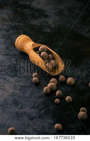 Wooden Spoon Full Of Allspice On Vintage Dark Tray