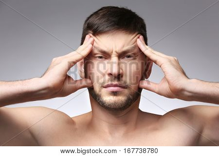 Young man with headache on color background