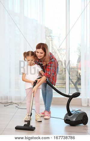 Pretty woman and her daughter hoovering floor at home