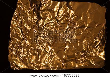Golden wrinkled wrapping foil texture. Crumpled aluminium shiny metal pattern on black background