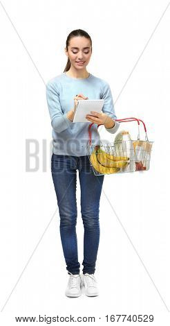 Young woman holding full shopping basket and checking grocery list on white background