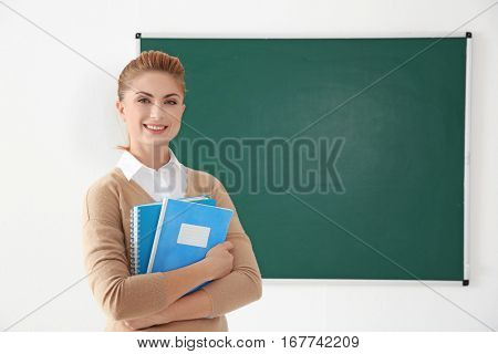 Young teacher with copybooks beside blackboard on white background