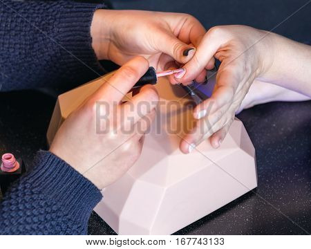 The manicurist holds hands of the client in beauty salon on desktop for manicure with nail polishes napkins creams and lighting instruments