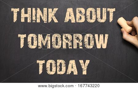Think about tomorrow today ! - Female hand writing text on blackboard.