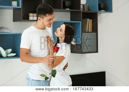 Man presenting red rose to girlfriend at home