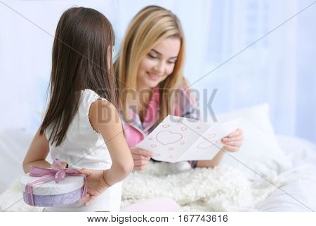 Cute little girl hiding present for her mother behind back. Mother's day concept