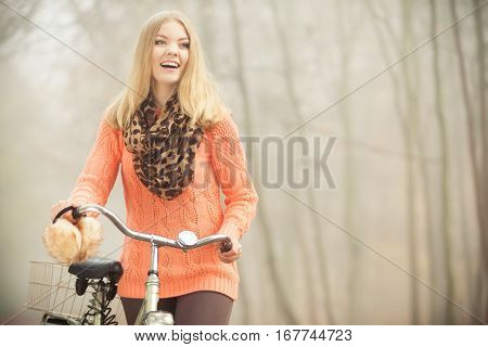 Happy active woman with bike bicycle in foggy fall autumn park. Smiling young girl in sweater relaxing. Healthy lifestyle and recreation leisure activity.