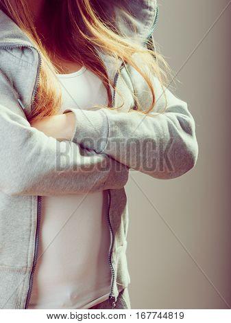Closeup of rebellious teenager crossing arms wearing sweatshirt.