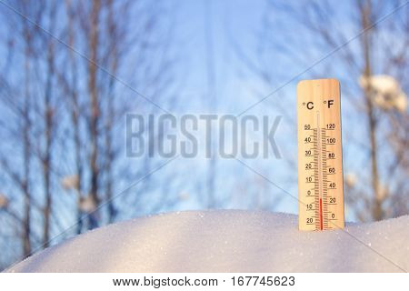 Thermometer in the snow on a background of sky and trees a bright Sunny day