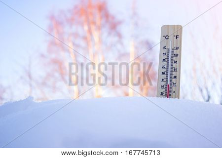 Winter thermometer in the snow against the sky a bright Sunny day