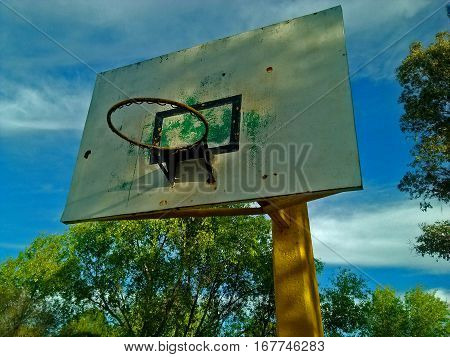 View of basketball hoop in the morning with a clear sky and trees around