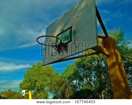 Basketball hoop seen from this angle, appreciating the trees that surround it