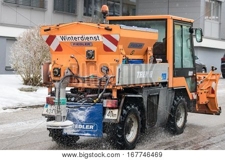 Upper Austria, AUSTRIA - January 312017: Snowplow removing snow from street and sprinkled salt antifreeze.