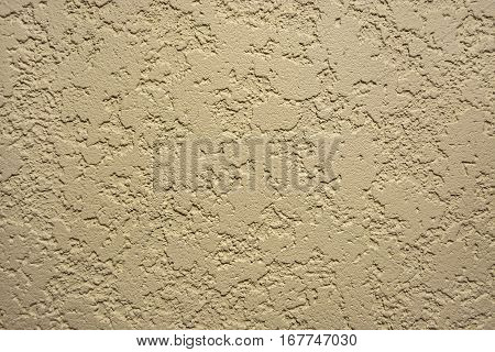 Abstract beige background of the spots of brown and white paint on the yellow plastered wall.