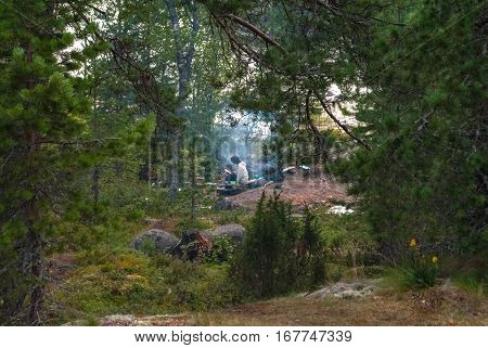 KARELIA LADOGA RUSSIA August 6: Tourists relax by the fire in the campaign on lake Ladoga in Karelia the evening of 6 August 2016.