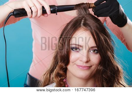 Hairdresser curling woman hair with electric iron curler tong. Hairstylist making girl hairstyle. Attractive pretty young female. Beauty.