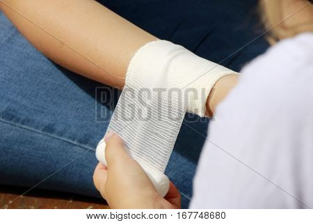 create pressure bandage of a wound on a forearm