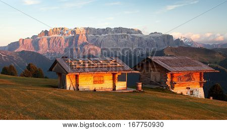Evening view of two small cabin and Sella Gruppe or Gruppo di Sella South Tirol Italian dolomities mountains Italy