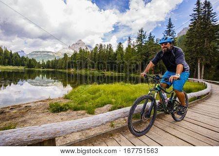 Mountain biking in the Dolomites, Misurina, Italy. Tre Cime di Lavaredo in background.