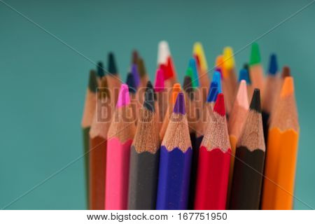 Multicolored pensils on a blue background. Back to school. Copy space. Top view.