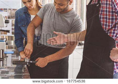 Concentrated man trying to compact coffee-powder into holder. Woman is looking at him