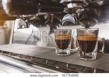 Two glassfuls of delicious dark coffee with light crema are at coffee-maker