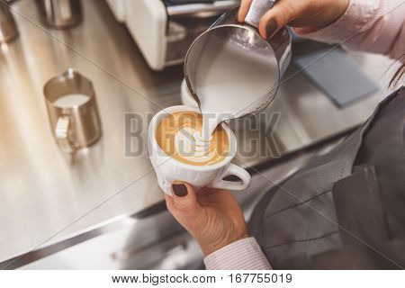 Female barista pouring shacked milk into little mug with coffee. She creating tracery