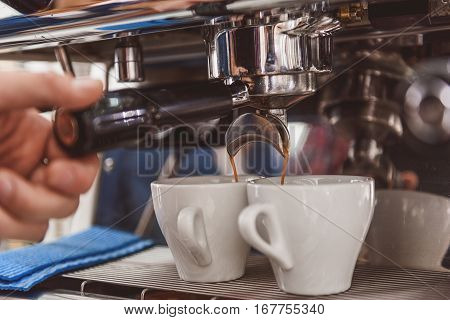 Coffee is pouring from special apparatus into little white mugs