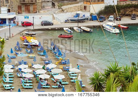 Bali Greece - April 30 2016: Sandy Mithos beach in sea bay of resort village Bali. Views of shore washed by waves and sun loungers with parasols where sunbathing tourists. Bali Rethymno Crete Greece