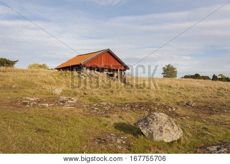 A small red farmhouse on the field